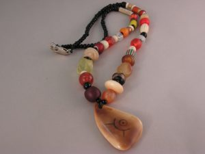Orange trade beads with Gooseberries and scrimshaw walrus tusk artifact
